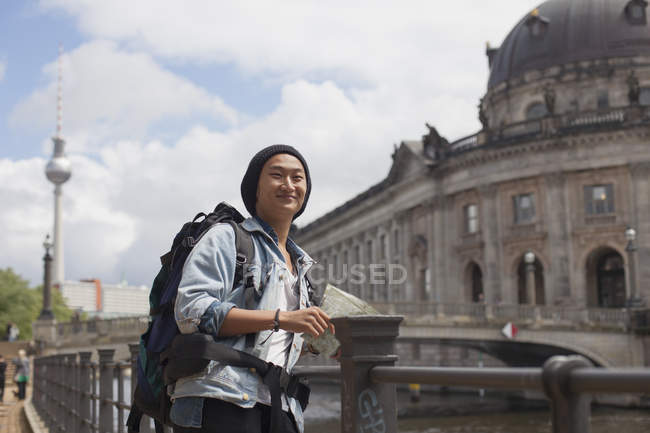 Smiling young male tourist standing with map by railing against Bode Museum, Berlin, Germany — Stock Photo