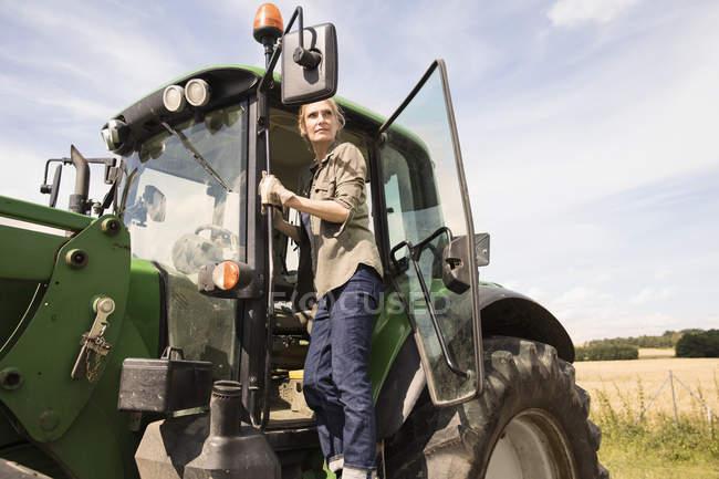 Frau stehend auf Traktor Farm gegen Himmel an sonnigen Tag — Stockfoto