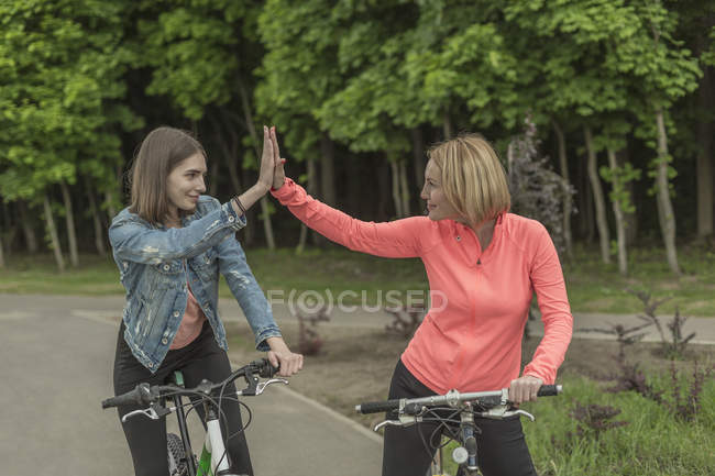 Smiling mother and daughter doing high-five while riding bicycles in park — Stock Photo