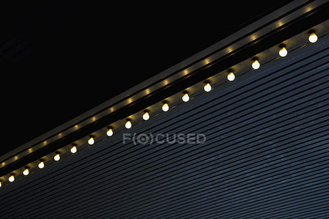 Low angle view of light bulbs in row on roof edge — Stock Photo