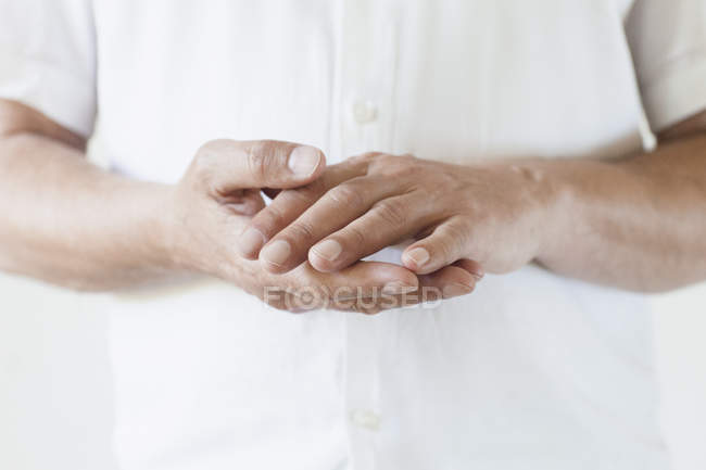 Midsection of man wearing white t-shirt with hands clasped — Stock Photo