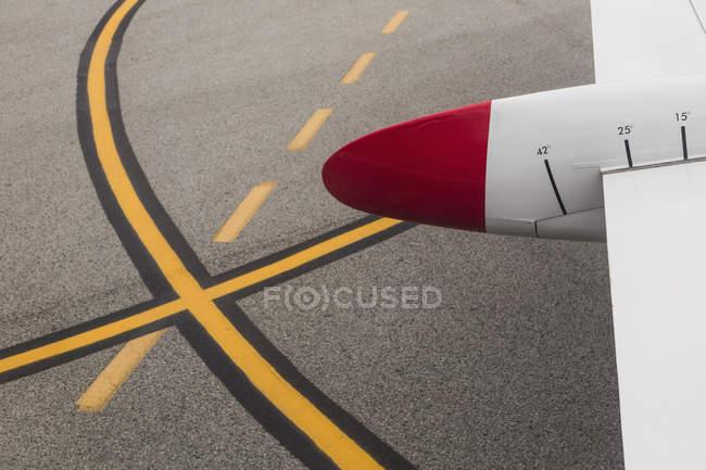 Abgeschnittenes Bild eines Flugzeugflügels auf der Landebahn des Flughafens — Stockfoto