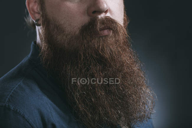 Male hipster with beard against gray background — Stock Photo