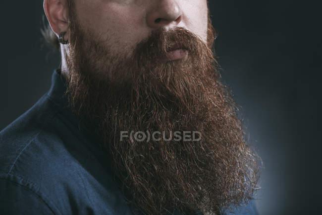 Männlicher Hipster mit Bart vor grauem Hintergrund — Stockfoto