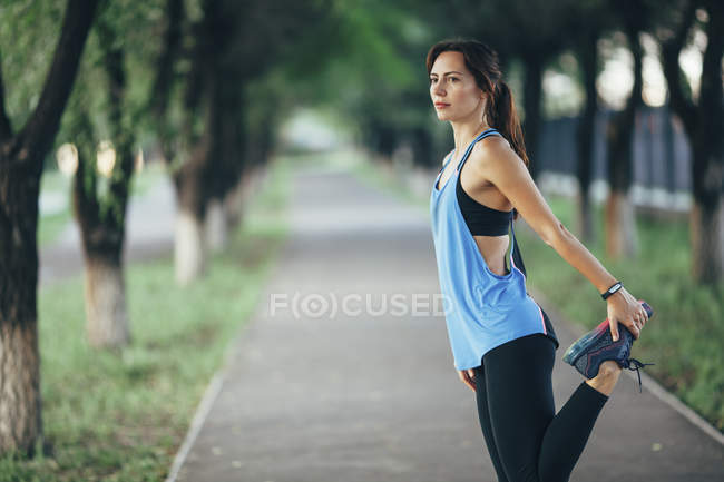 Young woman stretching on footpath at park — Stock Photo