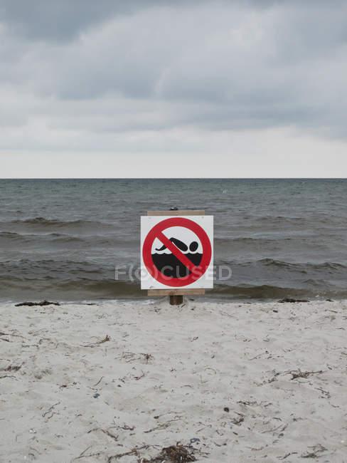 Немає купання знак на березі пісок моря — стокове фото