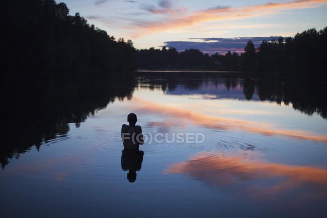 Vista trasera de un niño sin camisa parado en un lago tranquilo al atardecer - foto de stock