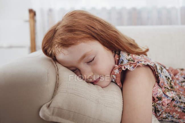 Cute redheaded girl sleeping on sofa at home — Stock Photo