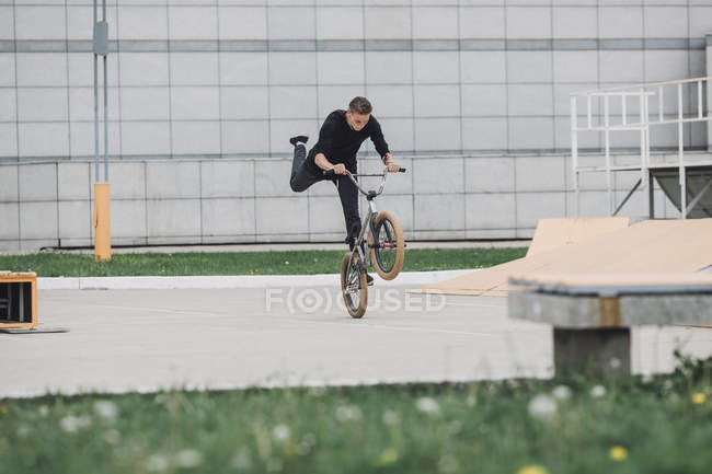 Teenager performing wheelie with bicycle at skateboard park — Stock Photo