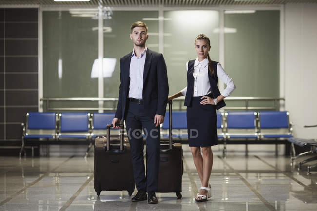 Portrait of young businessman and businesswoman with luggage in airport — Stock Photo
