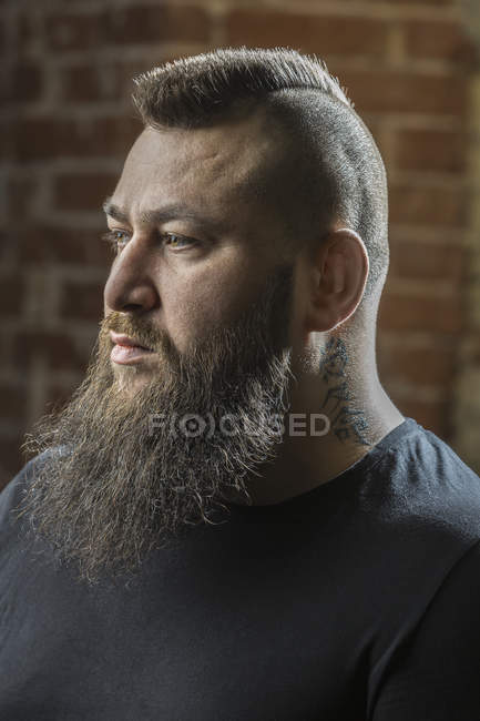 Close-up of male hairdresser with beard and tattoo looking away at barber shop — Stock Photo