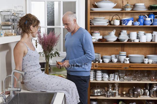 Älterer Mann kocht, während Frau auf Küchentisch sitzt und in der Küche zu Hause zusieht — Stockfoto