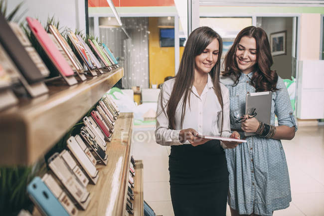 Young saleswoman showing brochure to female customer at electronics store — Stock Photo
