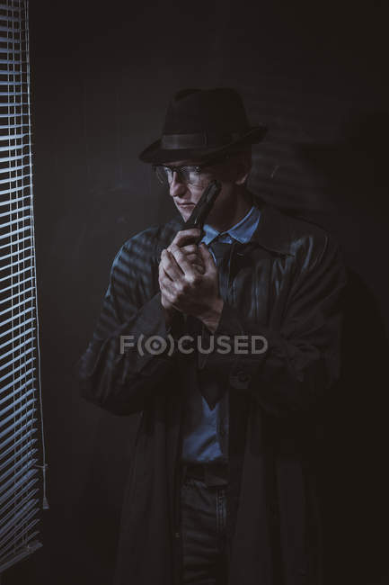Joven de pie con arma de fuego por ventana contra la pared negra - foto de stock