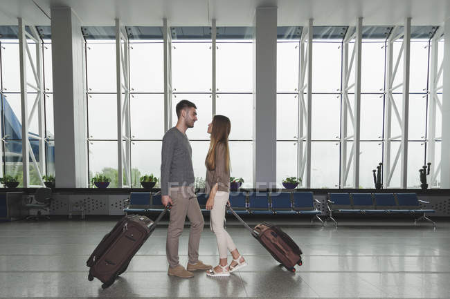 Young couple with luggage looking at each other at airport — Stock Photo