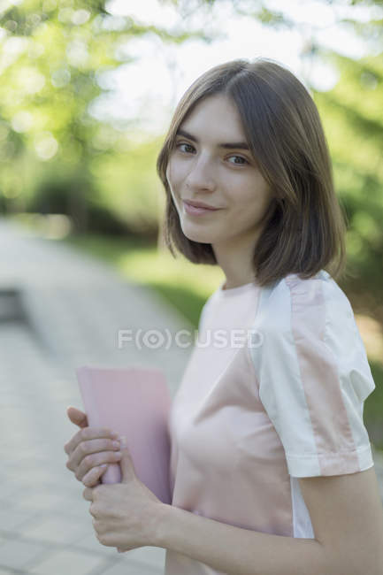 Portrait of smiling young woman holding digital tablet while standing in park — Stock Photo