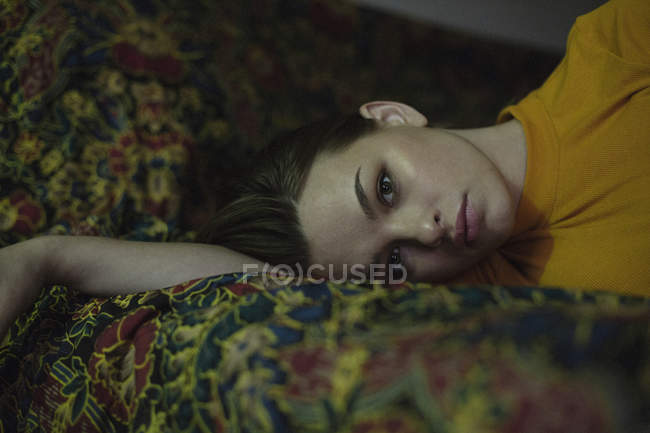 Portrait of beautiful young woman lying on bed — Stock Photo