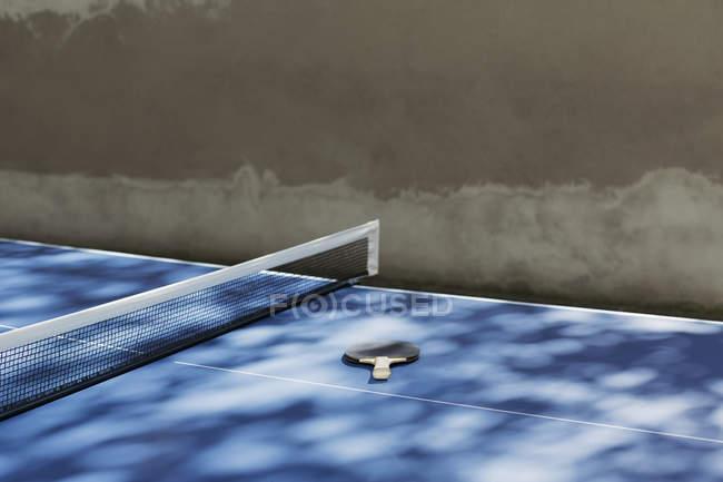 Tênis de mesa morcego deitado ao lado da rede na mesa — Fotografia de Stock