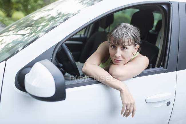 Portrait of woman resting in white car — Stock Photo