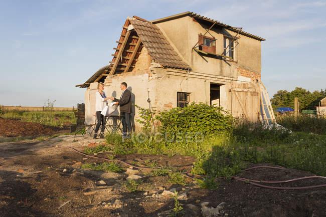 Agente inmobiliario estrechando la mano con el comprador mientras está de pie contra la casa residencial — Stock Photo