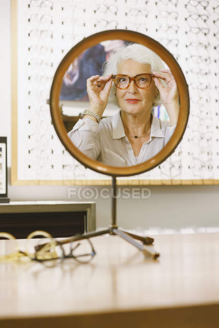 Portrait of senior woman wearing eyeglasses reflecting on mirror at store — Stock Photo