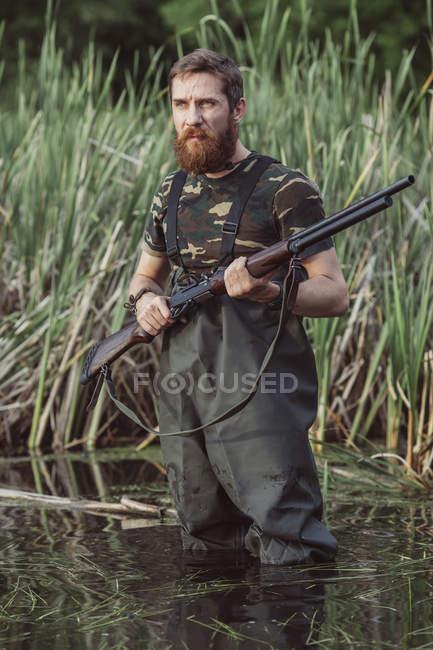 Cazador con pie de rifle en el lago por terreno herboso - foto de stock