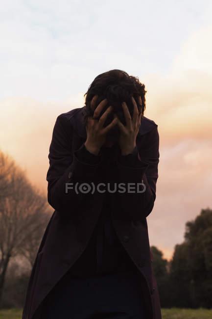 Mujer deprimida de pie con la cabeza en las manos contra el cielo puesta del sol - foto de stock