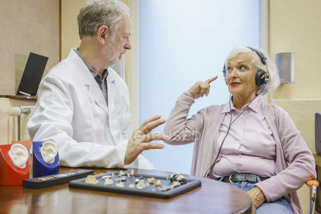 Senior patient wearing headphones talking to Audiologist during ear exam — Stock Photo