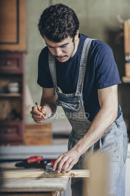 Carpenter marking on wood with pencil and ruler at workshop — Stock Photo