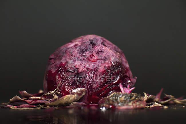 Nahaufnahme der Rübenwurzel mit Schalen auf dem Tisch vor schwarzem Hintergrund — Stockfoto