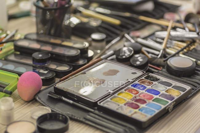 Vista de perto de vários equipamentos de maquiagem na mesa bagunçada — Fotografia de Stock
