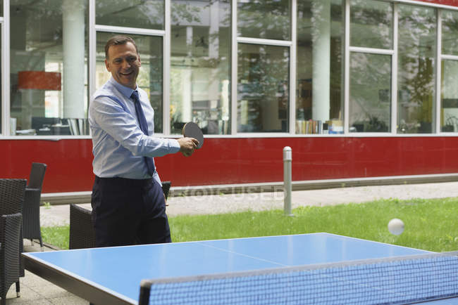 Confident happy businessman playing table tennis in creative office — Stock Photo