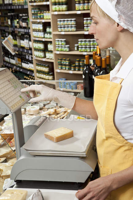 Sales clerk weighing  wedge of cheese in grocery store — Stock Photo