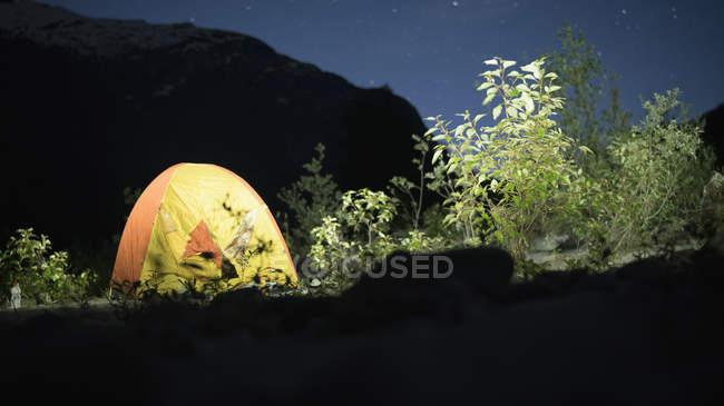 Tenda iluminada e arbustos contra a montanha à noite — Fotografia de Stock
