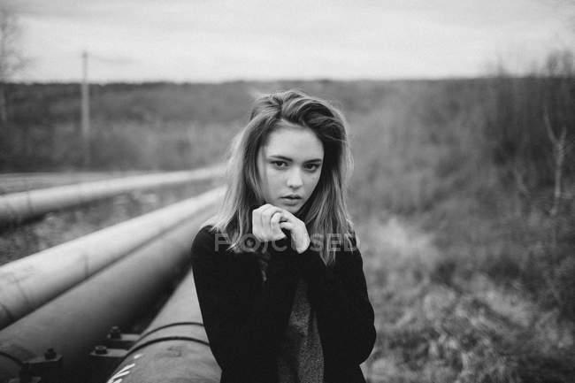 Портрет девочки-подростка с зажатыми руками, стоящей рядом с трубами на поле — стоковое фото