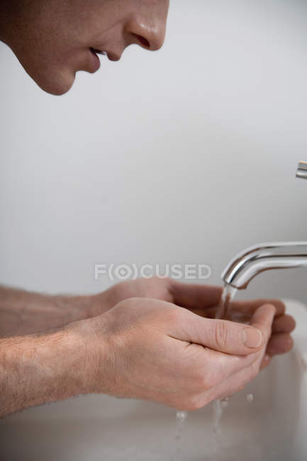 Crop man cupping hands under faucet — Stock Photo