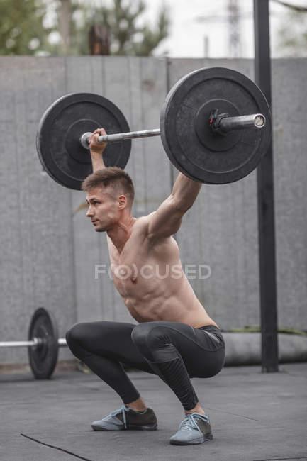 Nackter Oberkörper männlicher Athlet heben Langhantel beim Crossfit training — Stockfoto