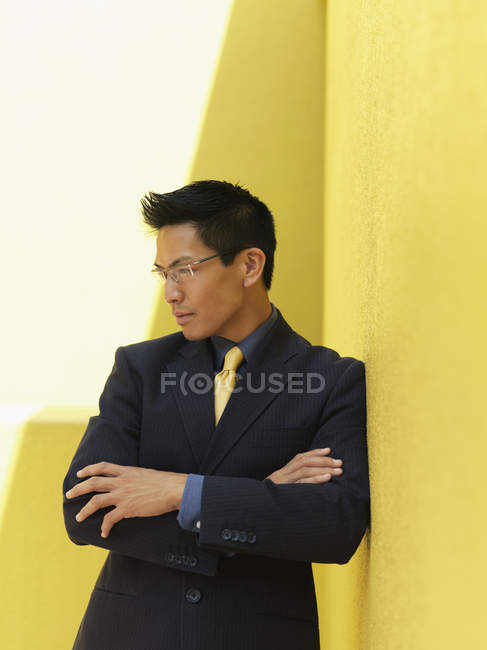 Portrait of businessman leaning on yellow wall with arms crossed — Stock Photo