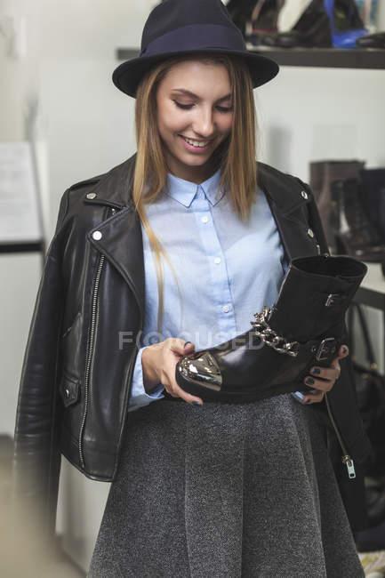Mulher feliz segurando sapato enquanto está na loja — Fotografia de Stock