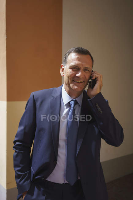 Happy businessman talking on mobile phone while standing in office — Stock Photo
