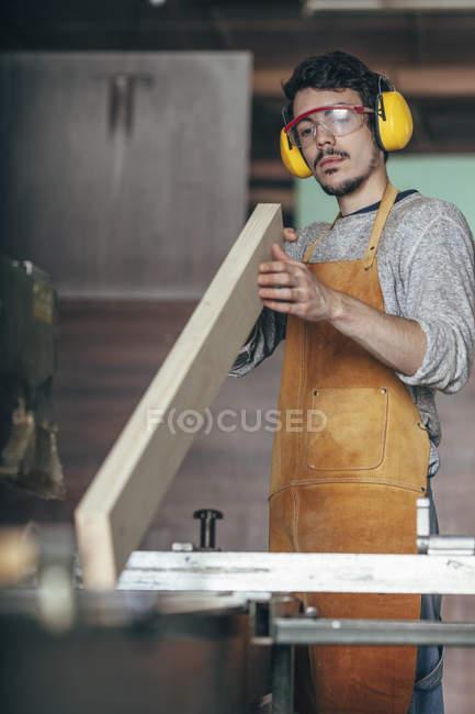 Carpenter examining plank of wood at workshop — Stock Photo