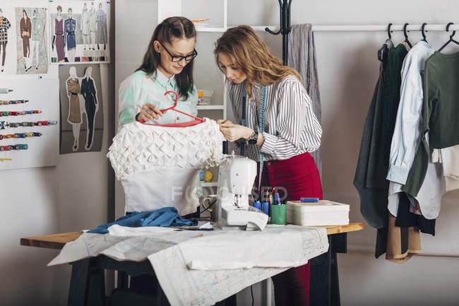 Стажер, вивчаючи тканиною сукні і дизайнер проведення вішалки в Ательє мод — стокове фото