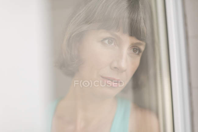 Portrait of mature woman seen through window glass — Stock Photo