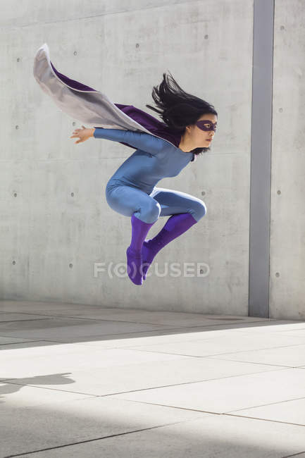 Female superhero levitating in mid-air against wall — Stock Photo