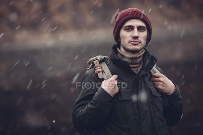 Портрет человека с рюкзаком на улице во время снегопада — стоковое фото