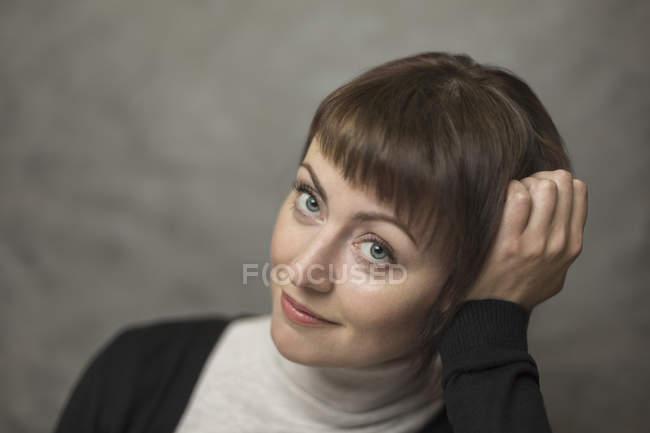 Ritratto di donna adulta sorridente con la testa in mano sullo sfondo grigio — Foto stock