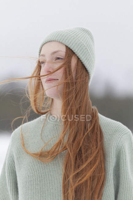 Nachdenkliche junge Frau mit langen roten Haaren mit Strickmütze und Pullover im Winter — Stockfoto
