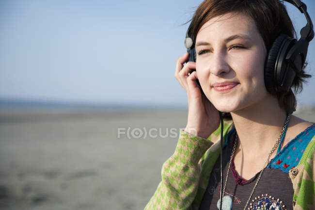 A woman listening to headphones at the beach — Stock Photo