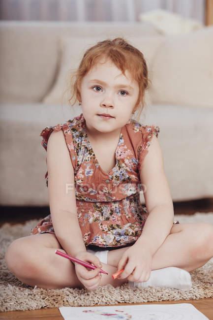 Симпатичная девушка рисует, сидя на ковре в гостиной дома — стоковое фото