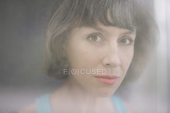 Портрет зрелой женщины через оконное стекло — стоковое фото
